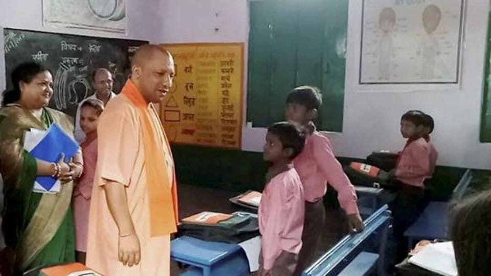 Uttar Pradesh chief minister Yogi Adityanath interacts with school children at a school at Brijghat in UP's Amroha.