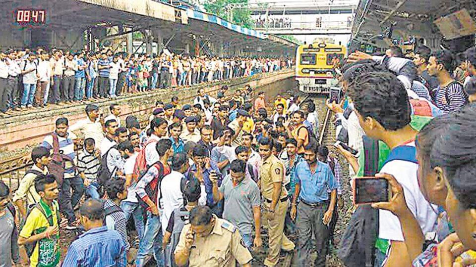 Commuters halt a train at Naigaon station near Mumbai on Saturday.