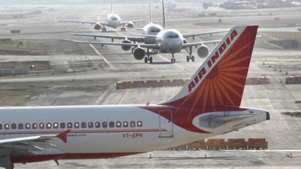 Air India aircraft parked near hangar at Mumbai airport.