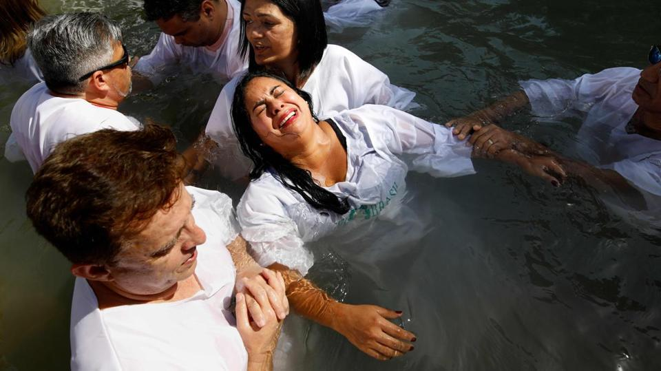 Evangelical Christian pilgrims from Brazil attend a mass baptism ceremony in the waters of the Jordan River at Yardenit in northern Israel during the Jewish holiday. According to the gospel Jesus Christ was baptized in the water of the Jordan River by John the Baptist. (Menahem Kahana / AFP)