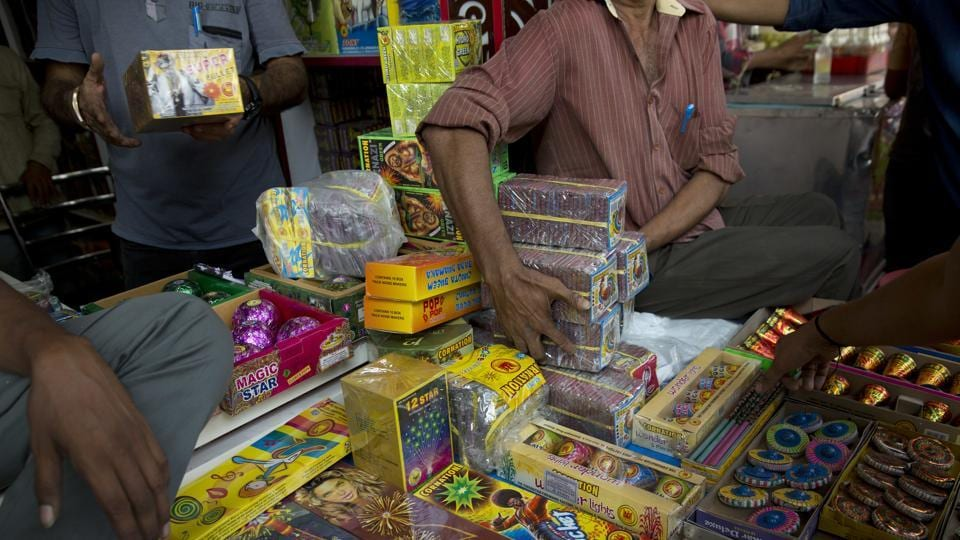 A shopkeeper hands over fire crackers to customers in New Delhi on Monday.