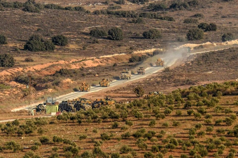 Turkish army armoured vehicles drive at the Syria-Turkey border on on October 8, 2017.