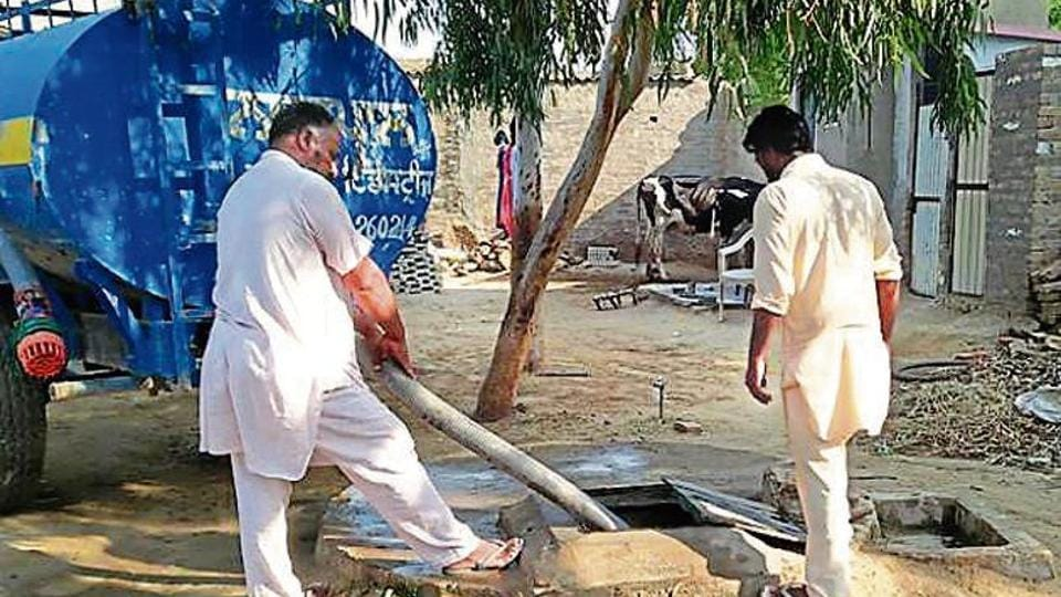 Residents filling up an underground storage tank with water from a tanker at Maan village in Muktsar district on Monday.
