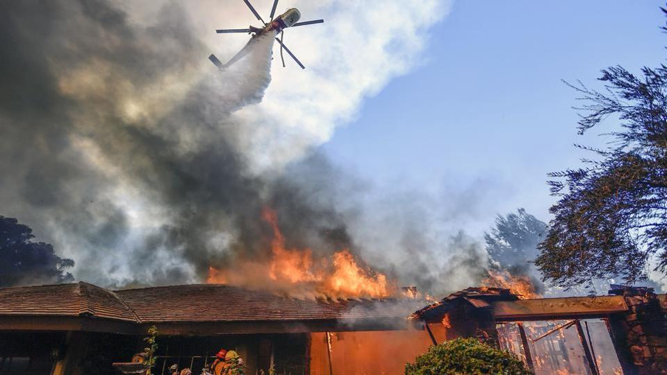 A helicopter dumps water on a home as firefighters battle a wildfire in Anaheim Hills, California. The fires are already among the ten deadliest in California's history. (Jeff Gritchen / AP)
