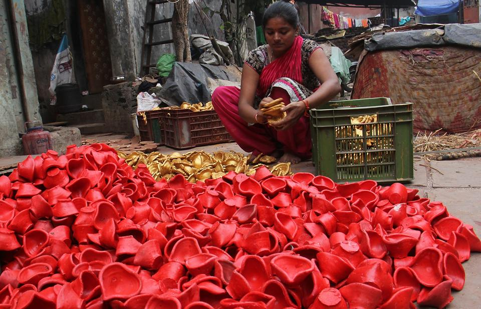 Eyes on target: An artist stacks up some of the ready diyas. (Pramod Thakur/HT Photo)