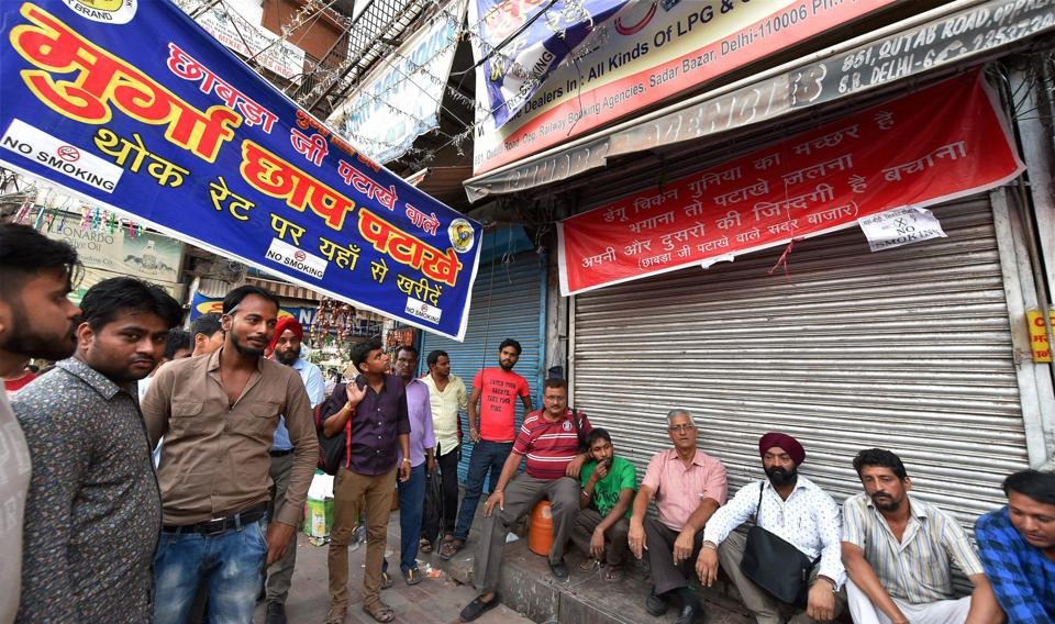 Shopkeepers sitting outside their closed shops of firecrackers at Sadar Bazar in New Delhi on Monday. The Supreme Court has banned the sale of firecrackers in Delhi till November 1.