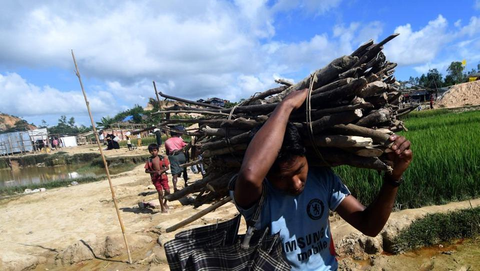 A Rohingya refugee carries woods in the Thankhali refugee camp in the Bangladeshi district of Ukhia on October 10, 2017. Several thousand Rohingya fleeing violence in Myanmar have taken refuge in Bangladesh, officials said, with reports of children dying from hunger, exhaustion and fever among the latest wave of refugees.