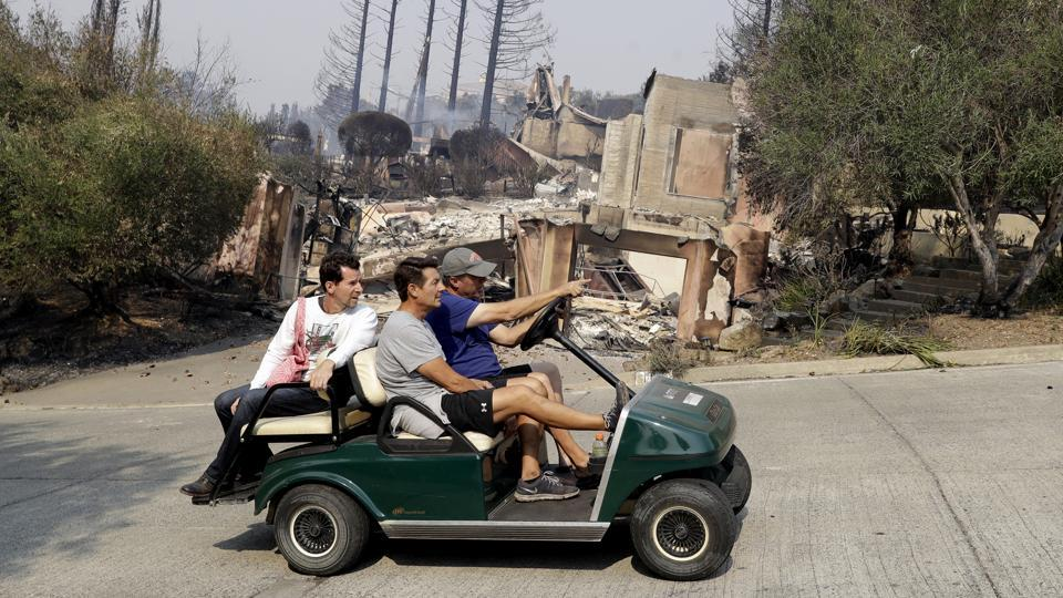 People drive by in a a golf cart in front of a fire-ravaged property in Napa, California. Governor Jerry Brown has  declared a state of emergency in Napa, Sonoma and Yuba counties. (Marcio Jose Sanchez / AP)