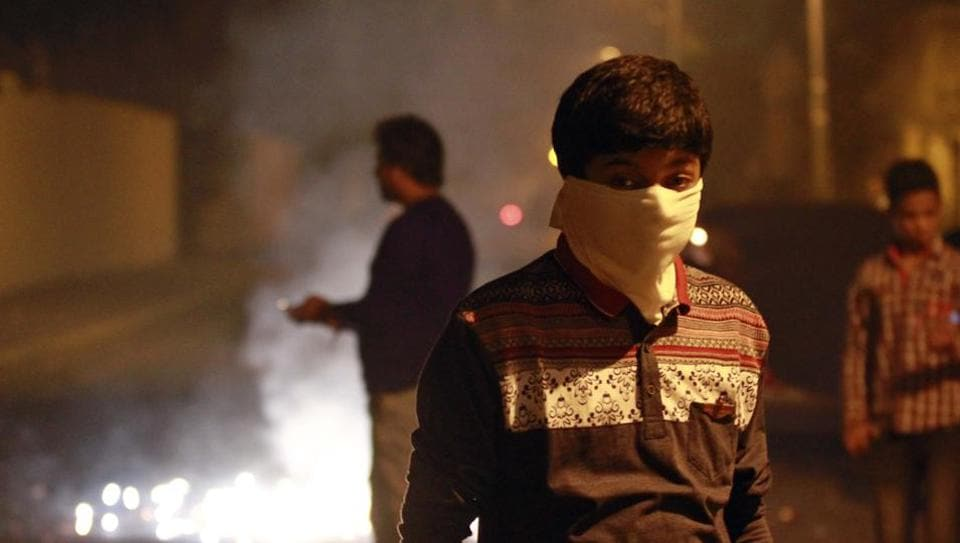 A boy covers his mouth as a man bursts crackers in the background on Diwali, in New Delhi.