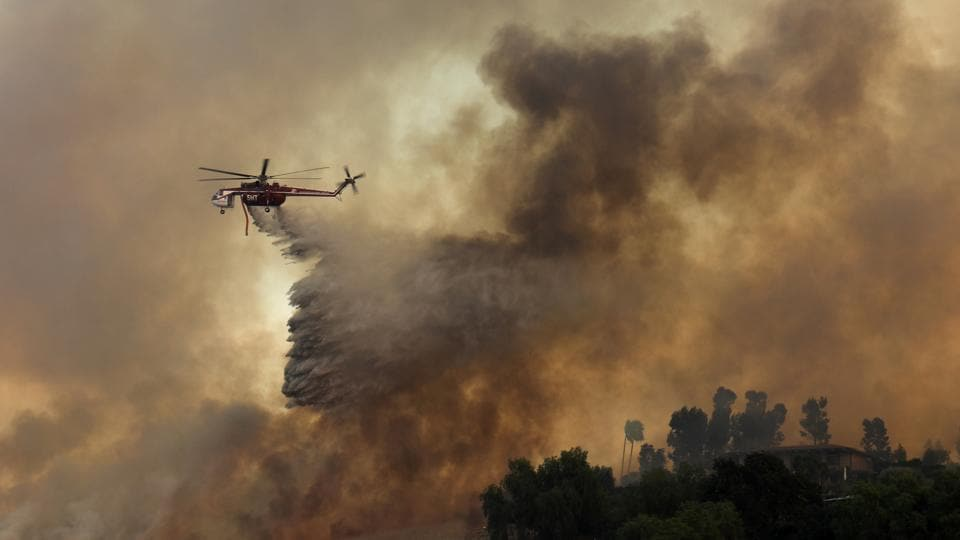 A firefighting helicopter drops water to help save a home during a wildfire in Orange, California.