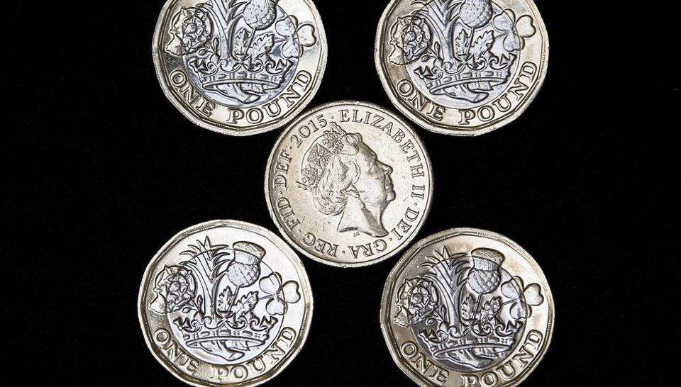 Photo shows an old issue one pound coin (centre) surrounded by newly issued 12-sided one pound coins.