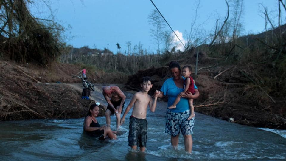 In the Puerto Rican village of San Lorenzo, Hurricane Maria destroyed the two-lane concrete bridge connecting residents with the outside world –making landfall on September 20, 2017. San Lorenzo remains without power or running water ever since. Like many remote villages, San Lorenzo now contends with a silent public health crisis in the wake of the strongest hurricane to hit the island in decades: isolation. (Alvin Baez / REUTERS)