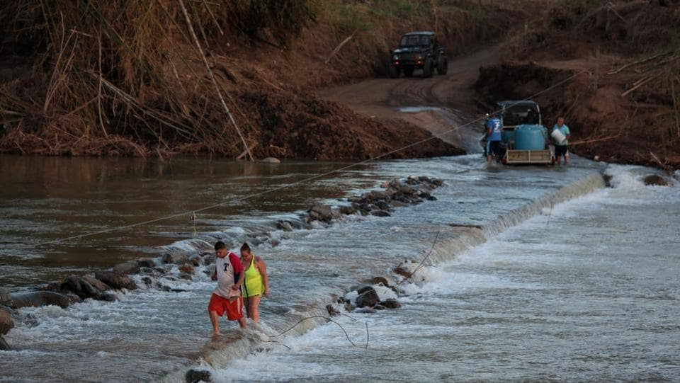 Local residents cross a river using a cable in lieu of the town's destroyed bridge in San Lorenzo.  (Alvin Baez / REUTERS)