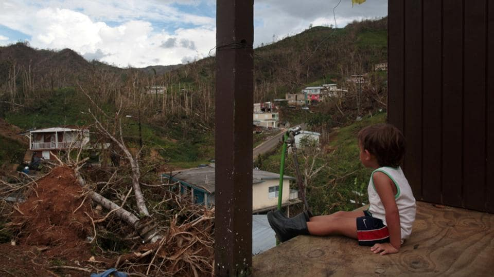 A boy looks out at his neighbourhood in the aftermath of Hurricane Maria in San Lorenzo, Puerto Rico. No one can say when - or if - the bridge will be rebuilt, but it is unlikely to be a high priority on an island with so many needs after the hurricane.  (Alvin Baez / REUTERS)
