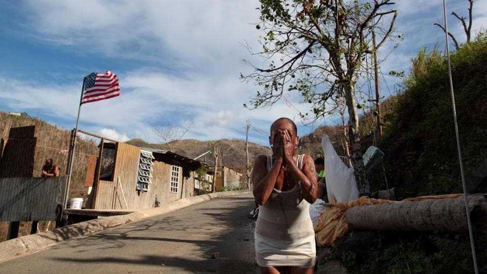 Ruth Santiago, a resident, refreshes herself with water from a pipe, lacking running water in San Lorenzo. Another resident said US officials came and took measurements after the bridge fell but nobody has returned and there is no word about plans for reconstruction. (Alvin Baez / REUTERS)