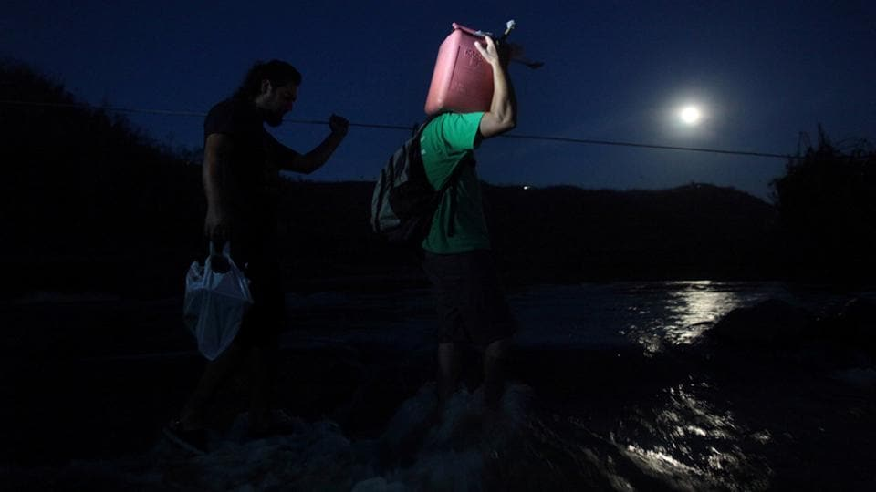 A local resident carries a gasoline can as he crosses a river using a cable in San Lorenzo. One other villager, dependent on dialysis treatment, was placed in a water barrel and pushed across the river by his neighbours.  (Alvin Baez / REUTERS)