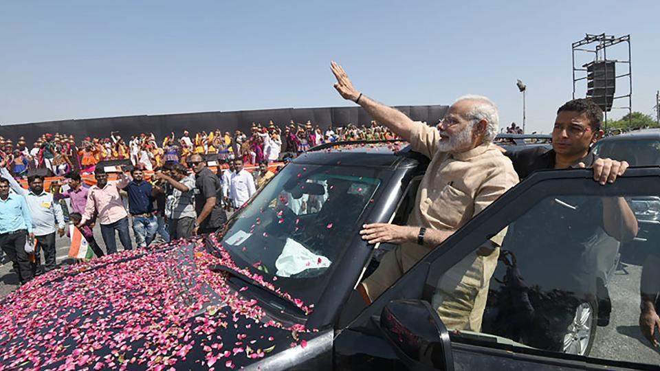 This handout photograph released by the Press Information Bureau (PIB) on October 8 shows Prime Minister Narendra Modi greeting people in Vadnagar in Gujarat.