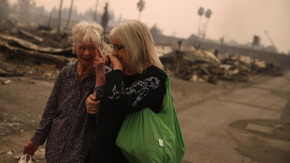 Residents walk through the fire-damaged Journey's End Mobile Home Park in Santa Rosa. Residents who gathered at emergency shelters and grocery stores said they were shocked by the speed and ferocity of the flames. Along with the damage to the environment, the personal loss has been huge.  (Justin Sullivan / AFP)