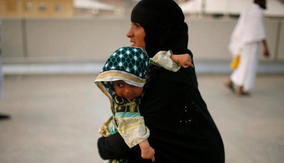 A woman holds a baby as she walks during the annual haj pilgrimage in Mena, Saudi Arabia September 1, 2017.