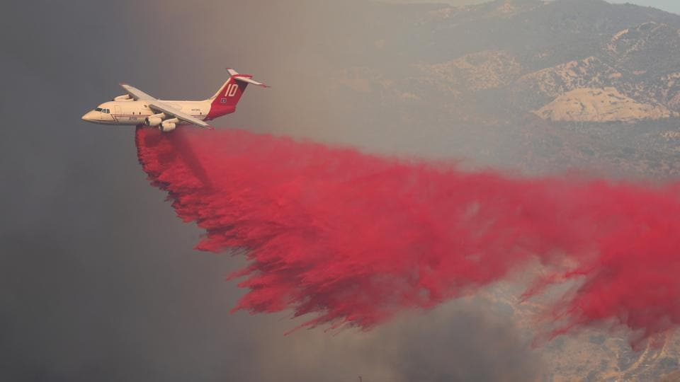 A firefighting aircraft drops fire retardant on a wind driven wildfire in Orange, California. 'The fires that broke out Sunday burned at explosive rates because of 50 mph winds,' said Ken Pimlott, director of the California Department of Forestry and Fire Protection. (Mike Blake / REUTERS)