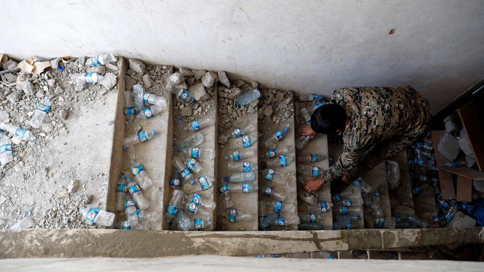 A fighter of Syrian Democratic Forces places empty plastic bottles on stairs of a building at their positions, at the frontline in Raqqa to squeak when stepped on and alert them to intruders. SDF fighters are well prepared in case the cornered IS militants attempt a breach. The front porch steps have been demolished, leaving a drop to the basement that can be crossed only by climbing a makeshift ladder, which can be pulled up. (Erik De Castro / REUTERS)