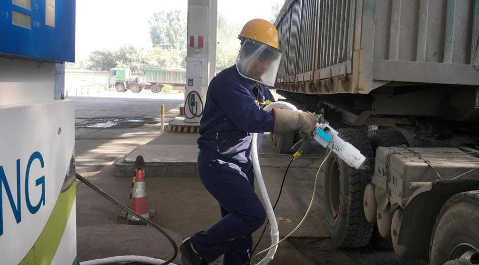 A worker prepares to fuel liquefied natural gas (LNG) for a LNG truck at a gas station.