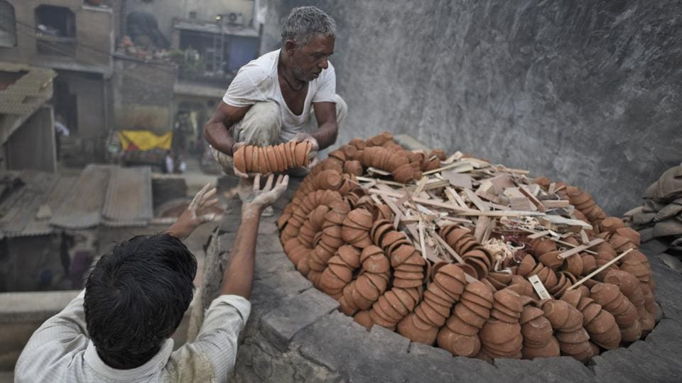 Located on the periphery of western Delhi in Uttam Nagar's potter's colony, generations have been using clay to mould earthen lamps, idols of deities and other festive ornaments. With the sale of firecrackers banned in Delhi and Diwali just around the corner, the production of these earthen lamps is on the rise. (Burhaan Kinu / HT PHOTO)