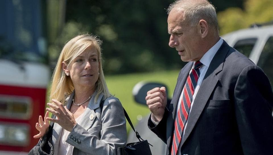 White House Chief of Staff John Kelly and Deputy Chief of Staff Kirstjen Nielsen speak as they walk across the South Lawn of the White House in Washington.