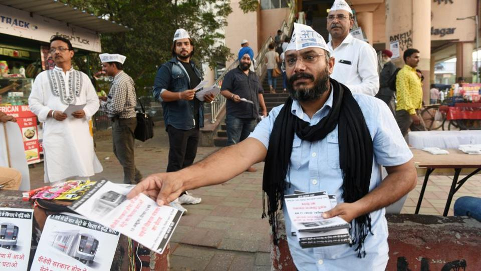 An AAP worker hands out pamphlets protesting the Metro fare hike near Lajpat Nagar Metro station on Wednesday.