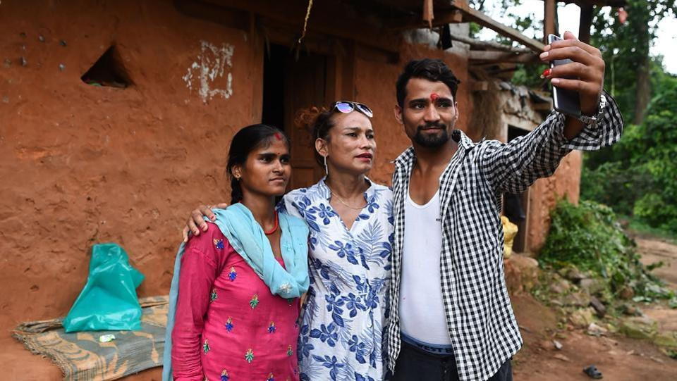 Here, Monika and Ramesh are seen taking a group selfie with Ramesh's first wife Laxmi Nath Yogi(first from left)at Kain Pani village in Nepal's Dadeldhura district. (Prakash Mathema / AFP)