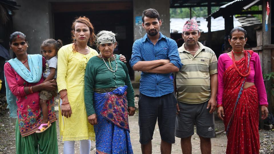 Nepali transgender person Monika Shahi Nath (3rd L) with Laxmi Giri Nath (L), the first wife of her husband Ramesh Nath Yogi (3rd R), Ramesh's youngest daughter Nabin Nath (2nd), Ramesh's grandmother-in-law Parbati Devi Nath (C), Ramesh's father-in-law Bhawani Nath (2nd) and Ramesh's mother-in-law Sita Devi Nath (R) in Kain Pani village in Nepal's Dadeldhura district. (Prakash Mathema / AFP)