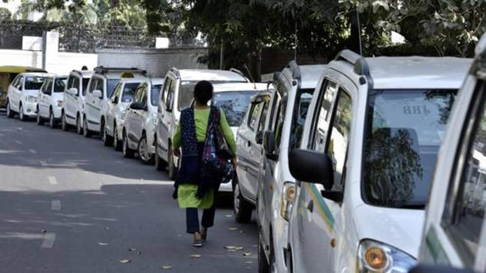 Ola and Uber cabs on the road in New Delhi.