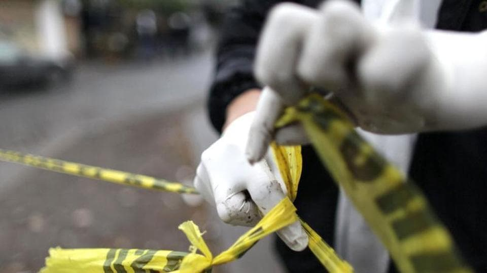 A forensic technician ties a used police line together to seal off a crime scene in Monterrey. Reuters Photo/Daniel Becerril