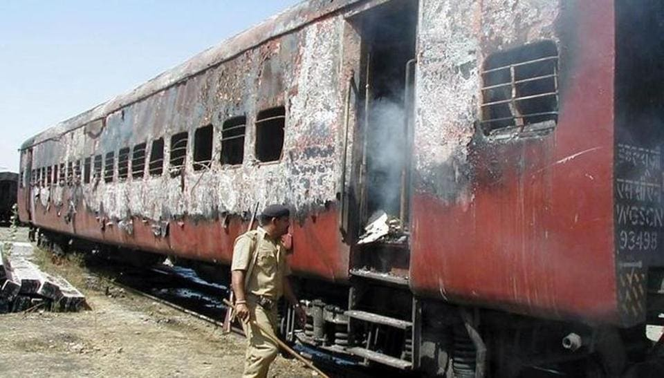 A policeman walks towards the entrance of a carriage of a train in Godhra on February 27, 2002.