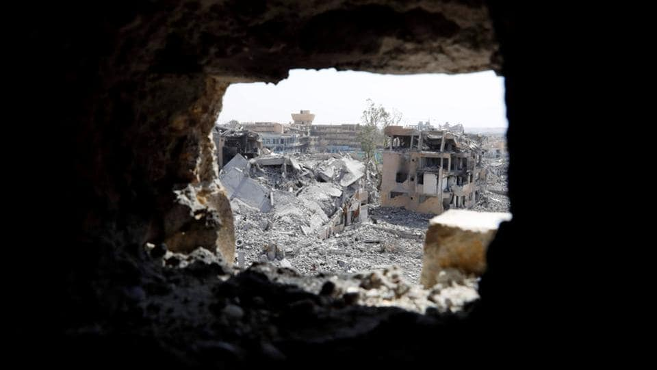 The Raqqa National Hospital, the last ISIS stronghold is pictured from a hole at the positions of the SDF at the frontline in Raqqa. In a gutted four-storey building turned into a fortress, Babel (his nom de guerre) and fellow SDF fighters can peer out at Islamic State positions just 150 metres away. (Erik De Castro / REUTERS)