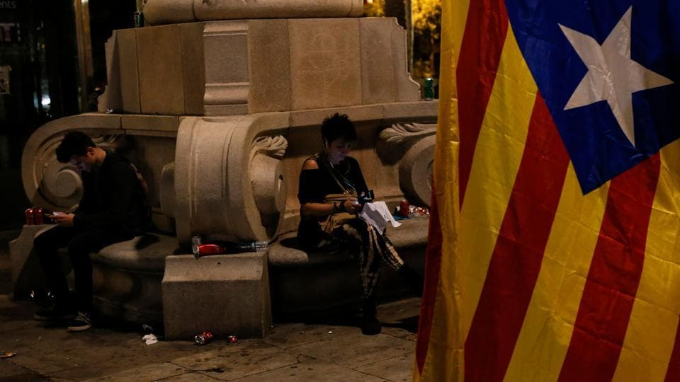 People check their phones next to a Catalan pro-independence 'Estelada' flag in Barcelona. Catalan leader Carles Puigdemont and his allies signed a declaration of independence for their region, which they nevertheless suspended pending talks with Madrid.