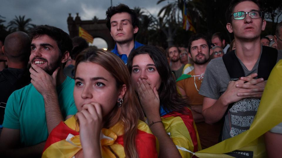 Supporters of an independence for Catalonia listen to Catalan president Carles Puigdemont's speech broadcasted on a television screen at the Arc de Triomf (Triumphal Arch) in Barcelona on October 10, 2017. Catalonia's leader Carles Puigdemont said he accepted the