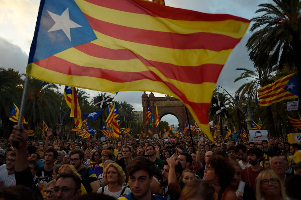 Supporters of an independent Catalonia listen to Catalan president Carles Puigdemont's speech broadcasted on a television screen at the Arc de Triomf in Barcelona on October 10, 2017.