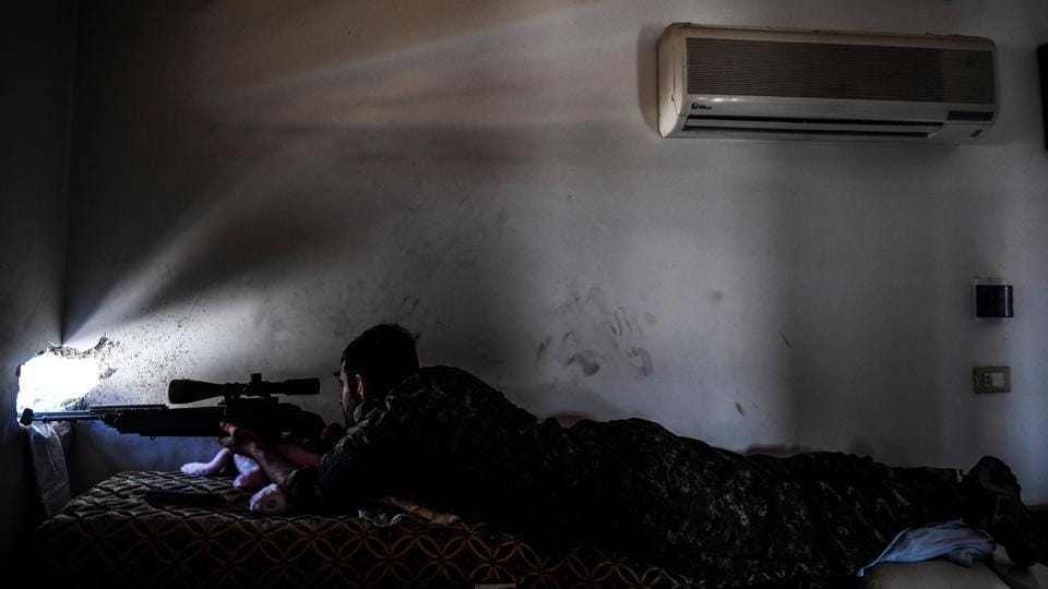 A member of the SDF, monitors ISIS positions on the western frontline in Raqqa. SDF are battling to clear the last remaining holed up jihadists, expected to make a last stand for their self-proclaimed caliphate --now cornered and desperate--  in Raqqa, the city on the Euphrates river that has served as their de-facto Syrian capital since 2014. (Bulent Kilic / AFP)