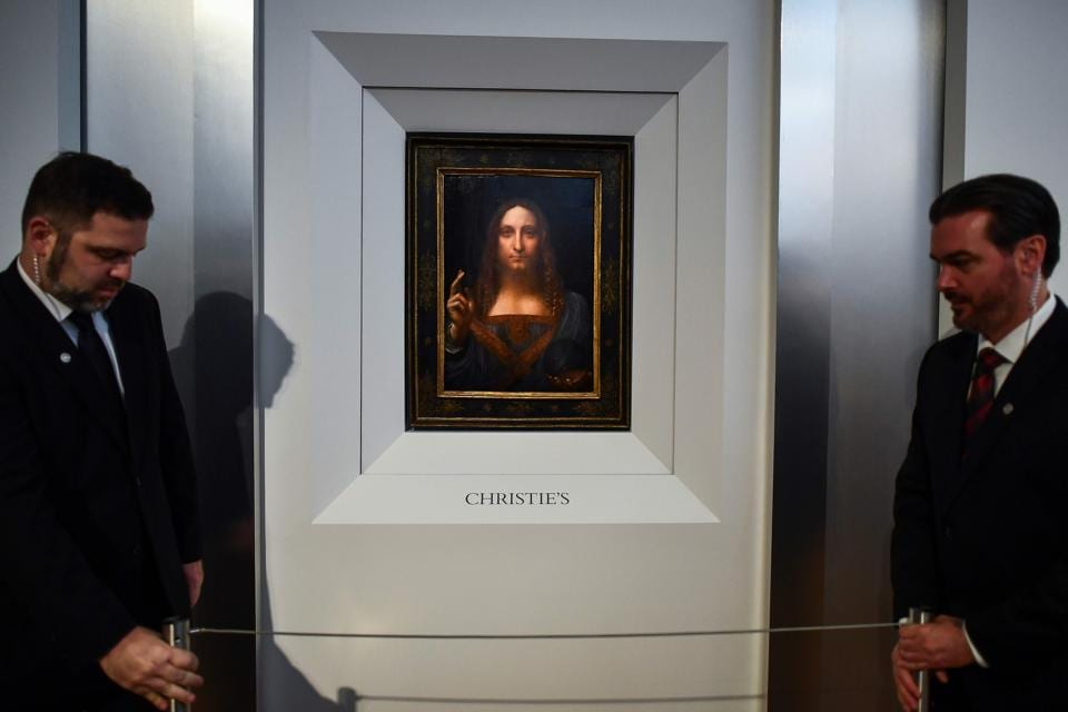 Security personnel stand next to Leonardo da Vinci's Salvator Mundi after it was unveiled at Christie's in New York on October 10, 2017.