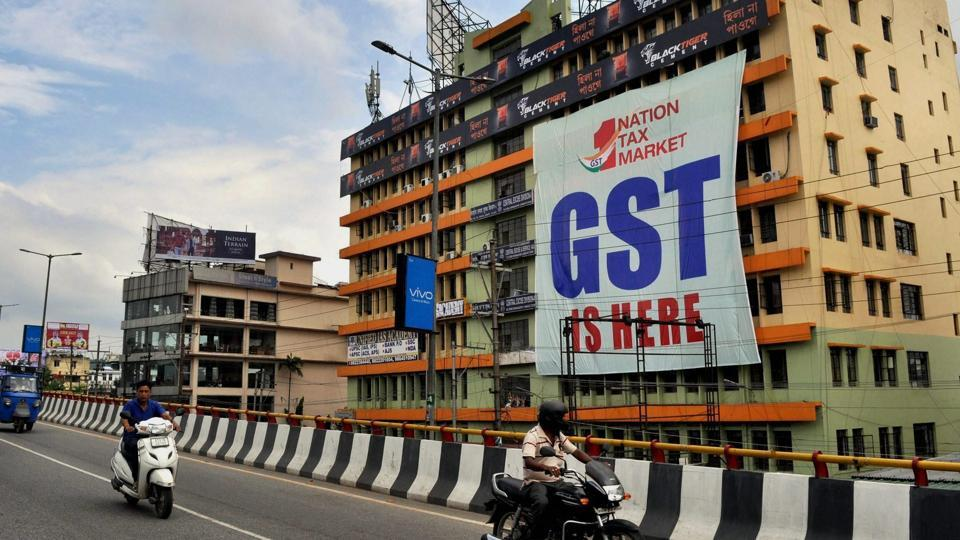 Vehicles move past a huge GST poster on the wall of a building, in Guwahati.