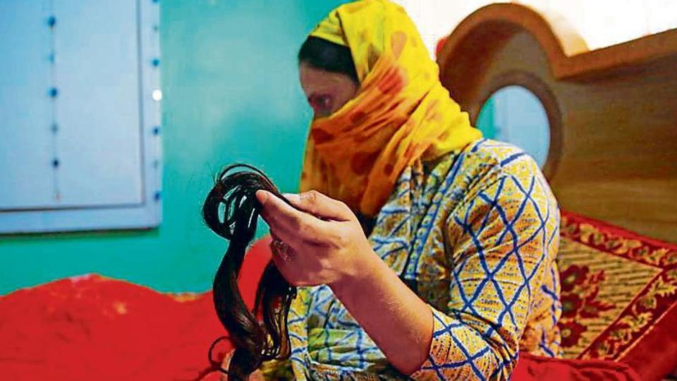 A woman displays her lock of hair that was chopped earlier this month in Srinagar.
