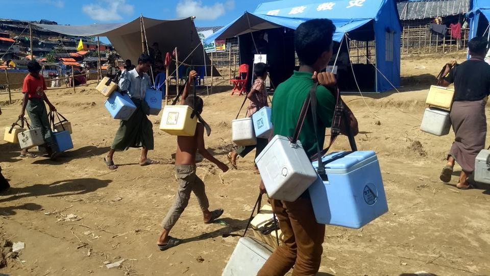 Rohingya volunteers carry ice boxes with cholera vaccines for inoculation at the Thangkhali refugee camp in Ukhia district. (Indranil Mukherjee / AFP )