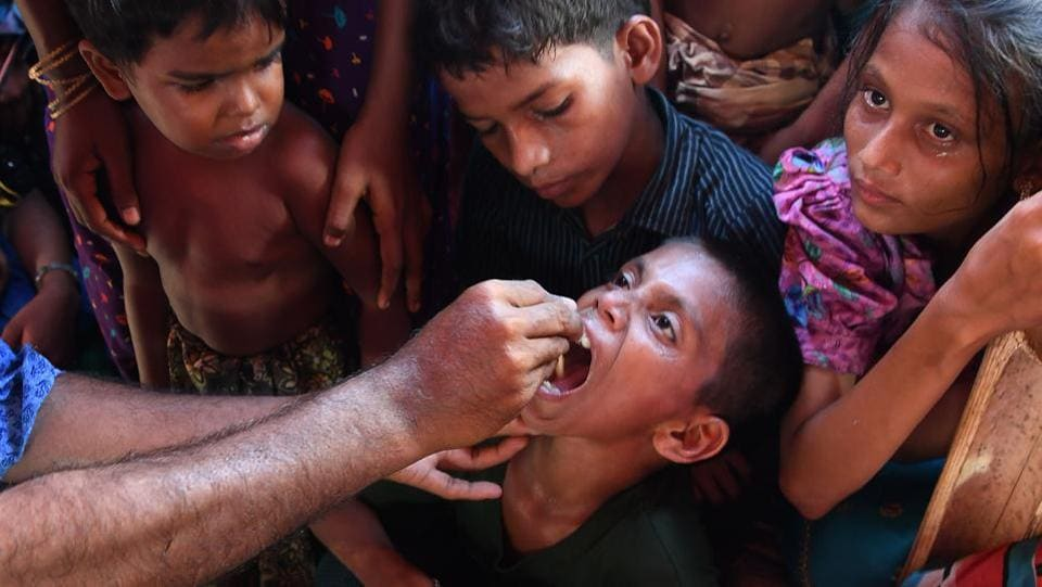 Rohingya refugee children look on as a Bangladeshi volunteer administers an oral cholera vaccine at a refugee camp. The World Health Organisation (WHO) on Tuesday launched a pre-emptive oral cholera vaccination campaign, the second largest ever in history after Haiti's in 2016, at camps inhabited by the Rohingya anticipating a possible outbreak. (Indranil Mukherjee / AFP )