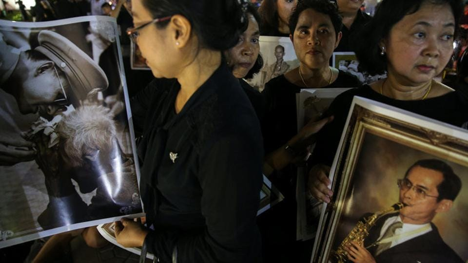 Well-wishers hold pictures of the late King Bhumibol Adulyadej on the last day the authorities allow people to pay their respect to the late king in the throne hall in Bangkok. Hundreds of thousands of black-clad mourners are expected to camp for days near Bangkok's Grand Palace to catch a glimpse of the ceremonies, which will be guarded by 78,000 police officers and culminate in the cremation on October 26. (Athit Perawongmetha / REUTERS)