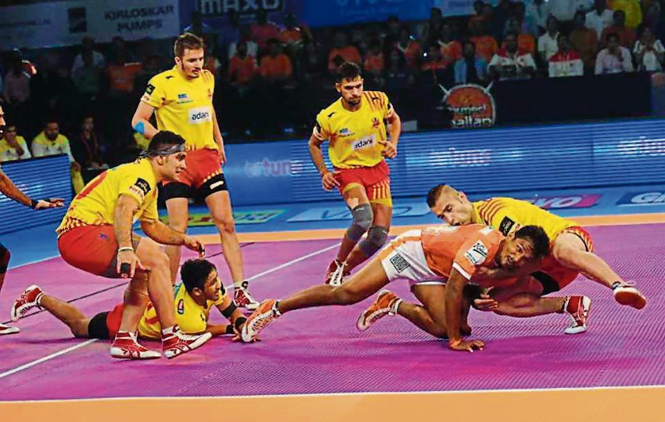Gujarat Fortunegiants tackle a Puneri raider during the Pro Kabaddi clash in Pune on Friday.