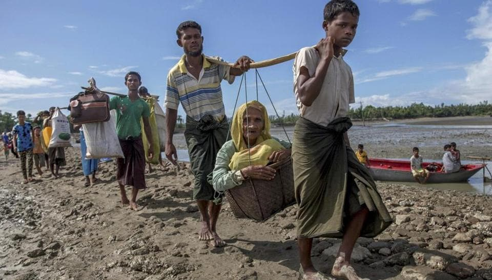 Rohingya Muslims, who crossed over from Myanmar into Bangladesh, carry an elderly woman in a basket and walk towards a refugee camp in Shah Porir Dwip, Bangladesh, inSeptember.