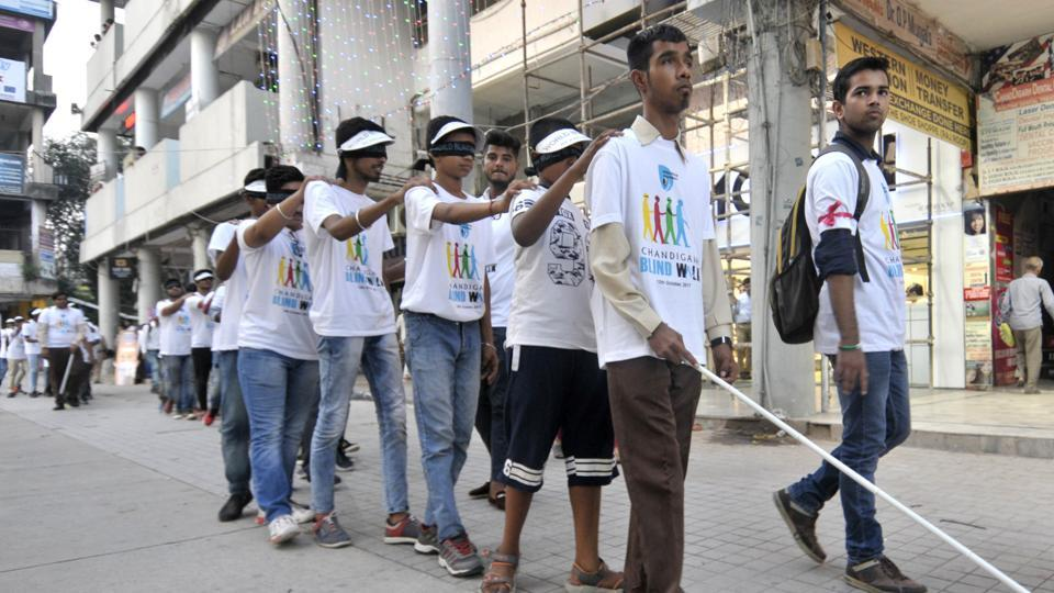A blind student at the head of a line of people who volunteered for an awareness walk in Sector 17, Chandigarh, on Thursday, October 12, which was World Sight Day.