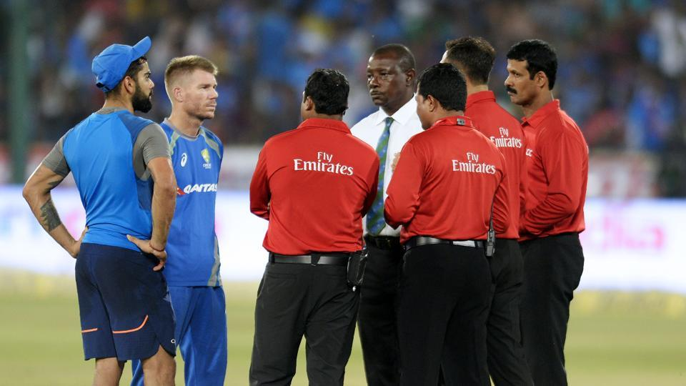 Virat Kohli (L) and David Warner (2L) talk to match referee Richie Richardson (C) and the umpires as play is delayed due to wet outfield on the third and final T20 cricket match between India-Australia at the Rajiv Gandhi International Cricket Stadium in Hyderabad. Catch full cricket score of India vs Australia here