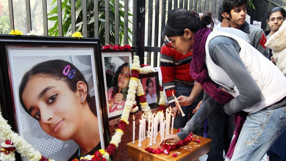 In this file photo friends and relatives of Aarushi Talwar light candles near her portrait to seek justice for her at Jantar Mantar in New Delhi in Jan 2011.